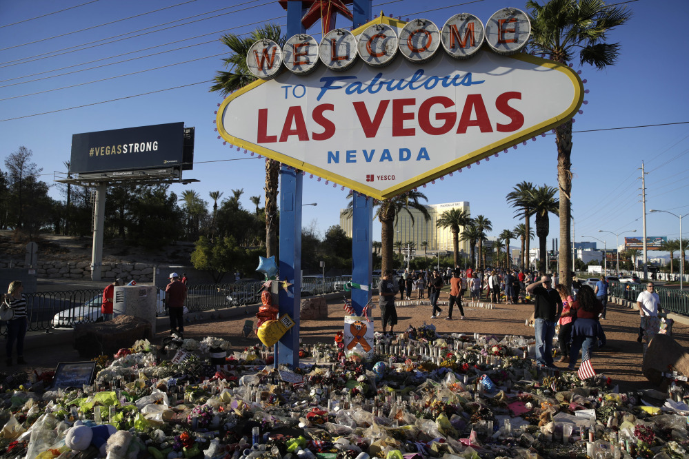 Flowers, candles and other items surround the famous Las Vegas sign at a makeshift memorial for victims of the mass shooting Oct. 1. Stephen Paddock opened fire on an outdoor country music concert, killing 58 and injuring hundreds.