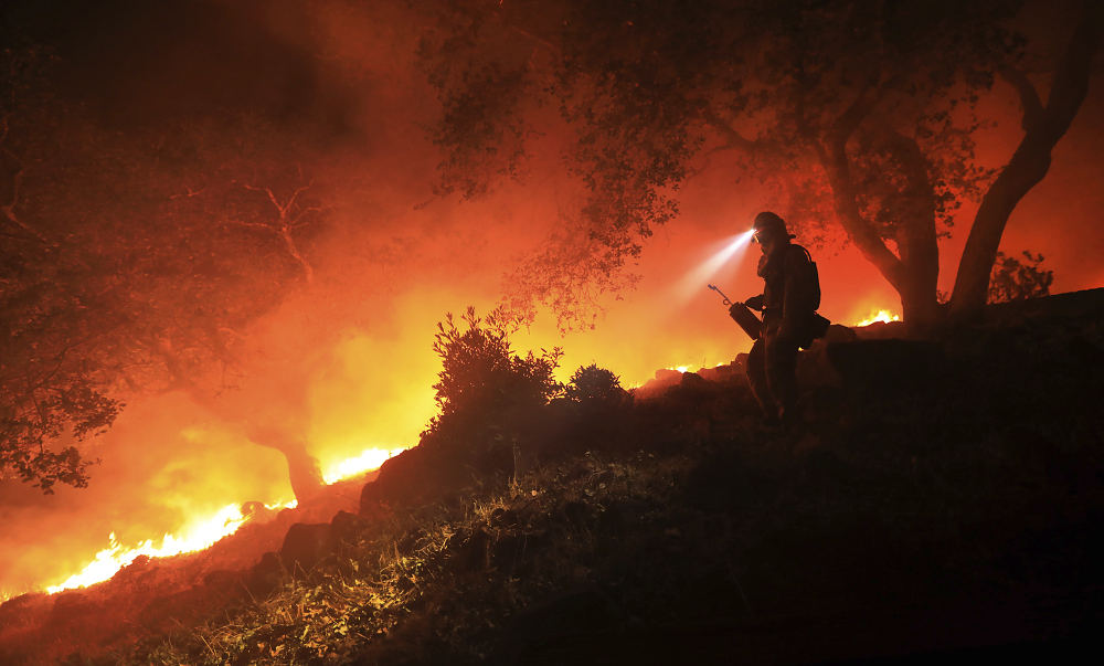 A San Diego Cal Fire firefighter monitors a flare-up on a the head of a wildfire above the Sonoma Valley on Wednesday in Sonoma, Calif. A wind shift caused flames to move quickly uphill and threaten homes in the area.