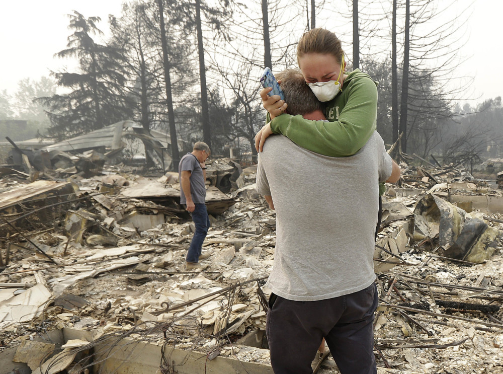 Todd Caughey, left, hugs his daughter Ella as they visit their destroyed home Tuesday in Kenwood, Calif. A fire official said Thursday that