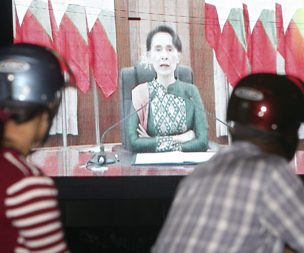 People stop to watch a speech by Myanmar's embattled leader, Aung San Suu Kyi, on Thursday. Suu Kyi has drawn criticism for failing to speak out as hundreds of thousands of Muslims have fled the country.
