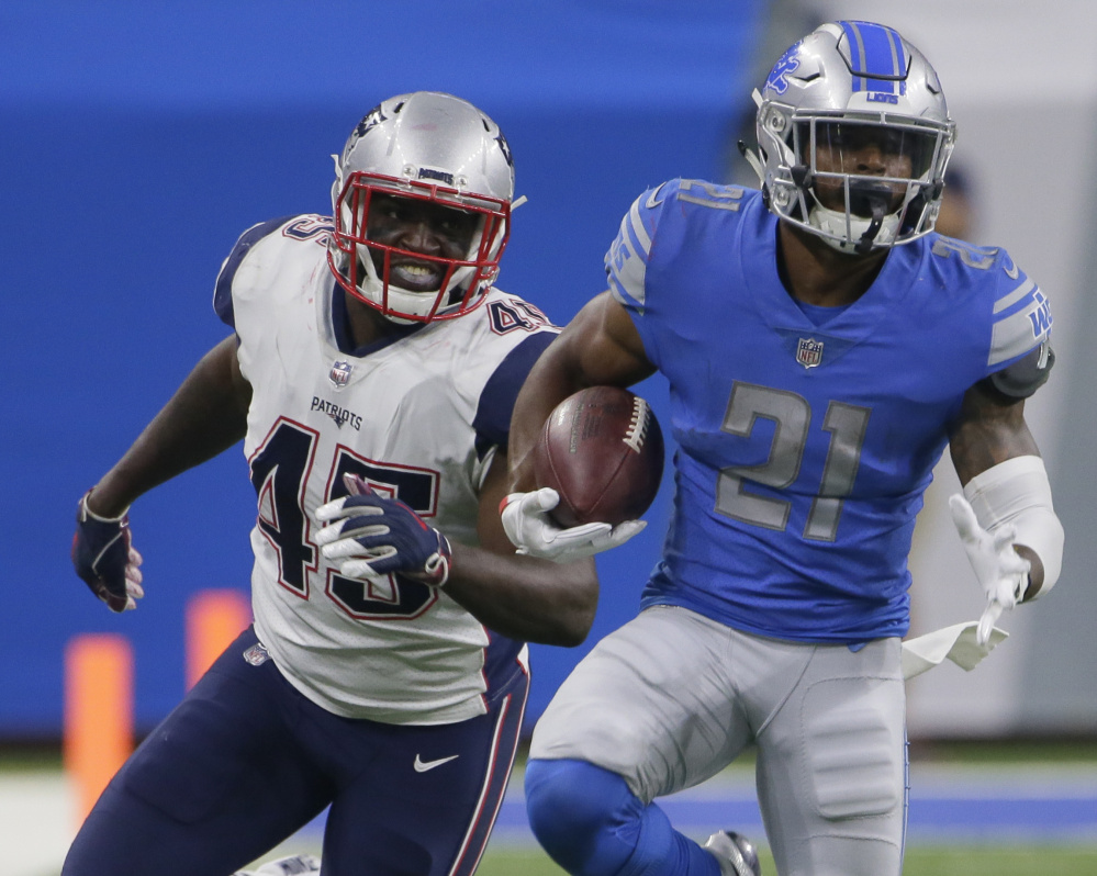 Detroit running back Ameer Abdullah looks for yardage during a preseason game as he is pursued by New England linebacker David Harris.