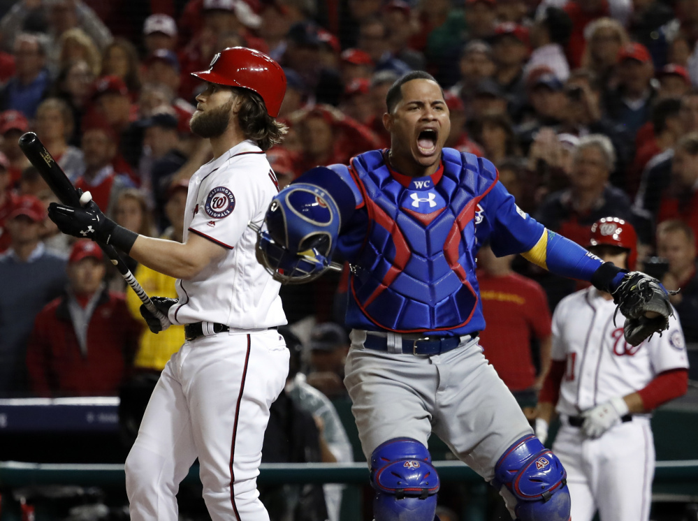 Cubs catcher Willson Contreras leaps after the Nationals' Bryce Harper struck out for the final out as the Cubs beat Washington 9-8 to to win their National League Division Series early Friday.