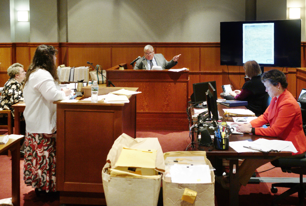 Retired Portland Police Detective Daniel Young answers a question from attorney Amy Fairfield during the fourth day of a post-conviction review for Anthony Sanborn on Friday. Below, Young looks over an investigative report.