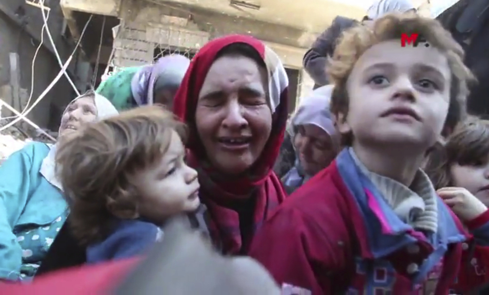 A Syrian woman weeps after she and her children fled from an Islamic State-controlled section of Raqqa, Syria. Mezopotamya Agency, via AP
