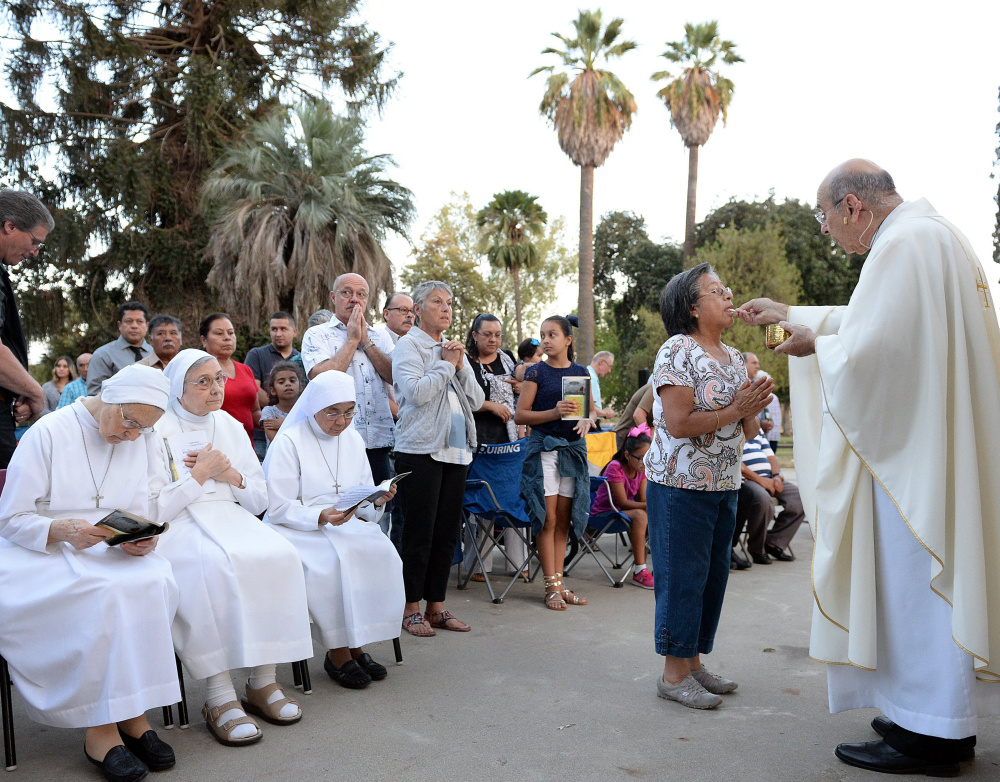 From a retrofitted trailer pulled by a truck, Bishop Armando X. Ochoa of the Roman Catholic Diocese of Fresno, Calif., gives Communion during a Mass at Kearney Park in Fresno as part of the diocese's 50th anniversary in September.