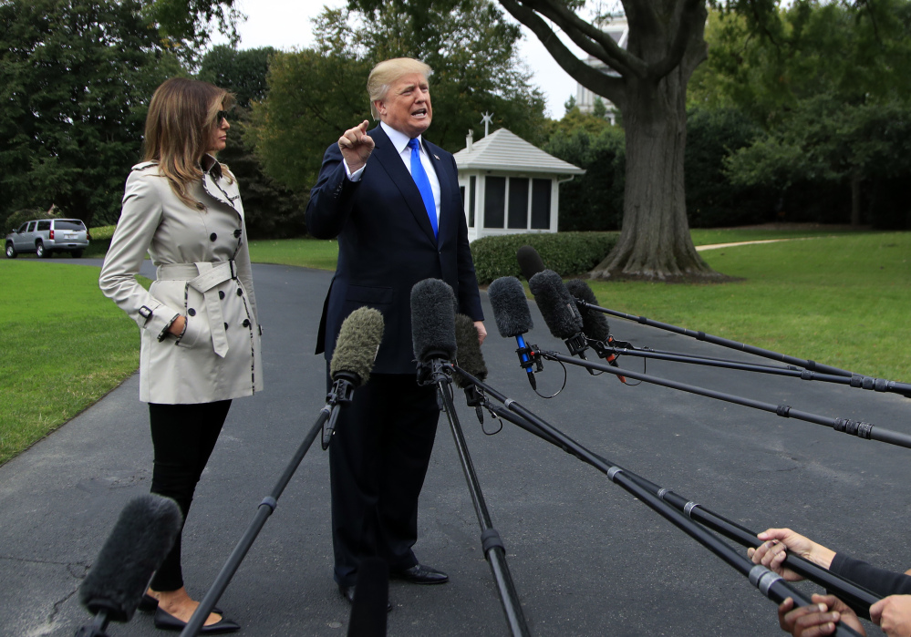 "President Trump, with first lady Melania Trump, speaks to reporters on the South Lawn of the White House on Friday. Trump said on Twitter, ""ObamaCare is a broken mess."""