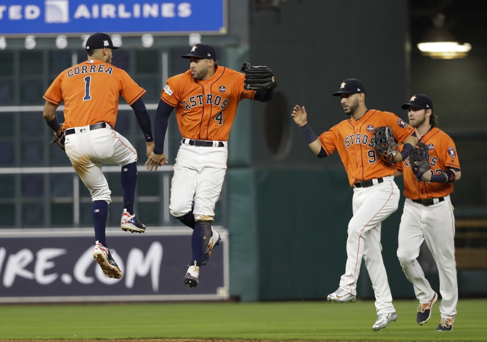 Houston Astros' Carlos Correa and George Springer celebrate after Game 1 of the American League Championship Series on Friday in Houston. The Astros won 2-1 to take a 1-0 lead in the series.