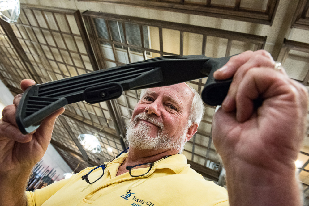 John Reid holds up a bump stock Saturday afternoon at his gun show. He said his shop in Auburn had sold out of the attachments in a couple of days in reaction to talk of a ban.