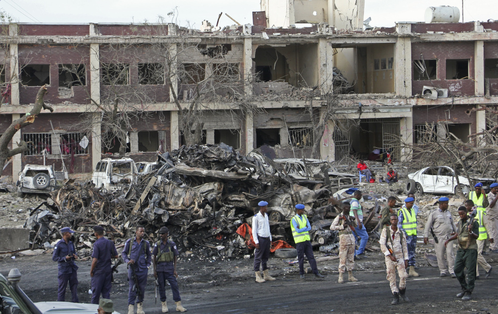 Somali security forces and others gather and search for bodies near destroyed buildings as hospitals struggled to cope with the high number of casualties.