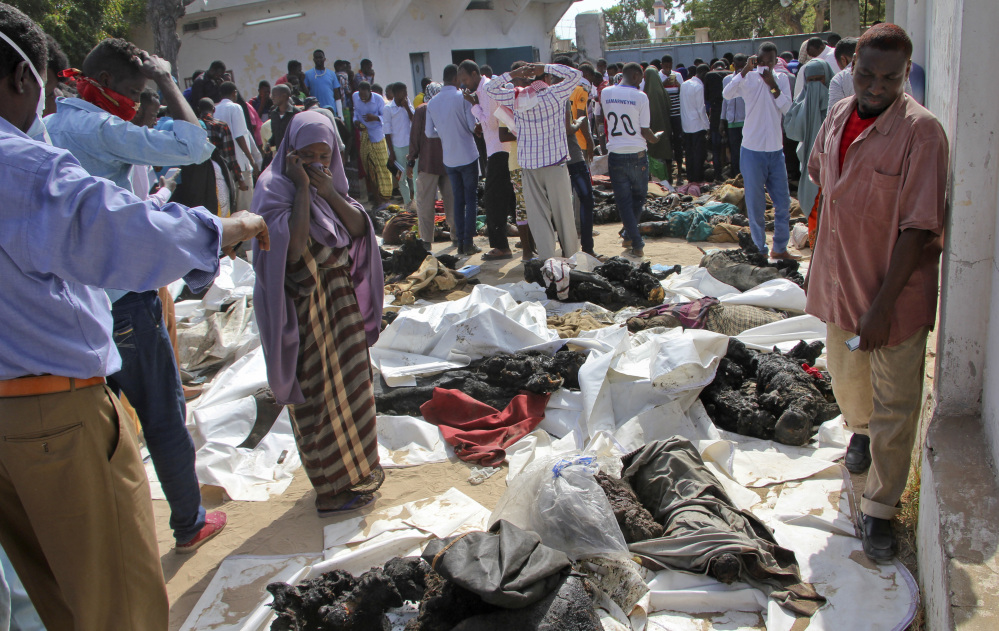 A Somali woman reacts as she stands by the remains of victims of Saturday's blast in Mogadishu on Sunday. The death toll from the most powerful bomb blast witnessed in Somalia's capital rose to at least 230 with more than 200 injured.