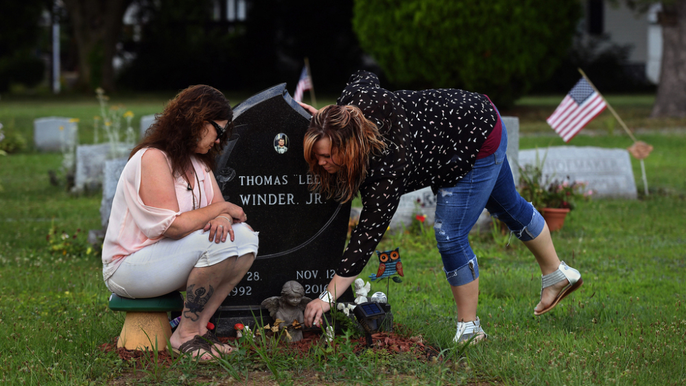 Tina Snyder, left, and Courtney Winder visit the grave of - respectively - their son and brother in July. The 24-year-old died of an opioid overdose in November. Winder lost another brother to an overdose in 2014. Must credit: