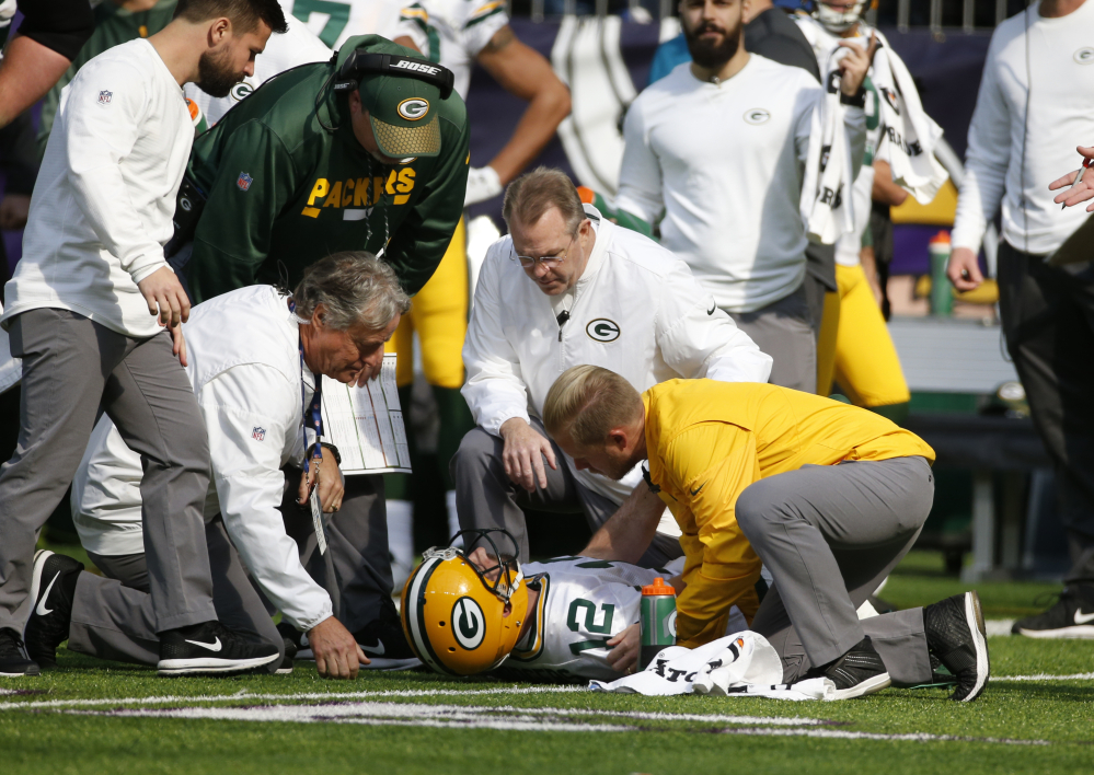 Packers quarterback Aaron Rodgers is checked by medical staff after being hit by Minnesota linebacker Anthony Barr in the first half Sunday in Minneapolis. The Packers later revealed that Rodgers has a broken collarbone and might have to miss the rest of the season.