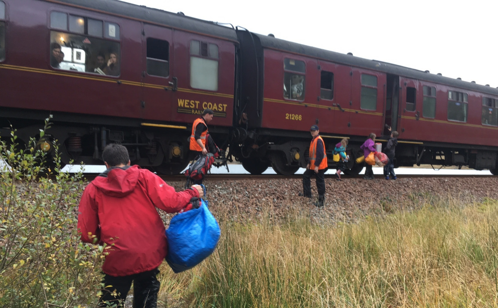 The Cluett kids run to the train that picked them up in the Scottish Highlands after the family canoe washed away. The train was known as Hogwarts Express in Harry Potter films.