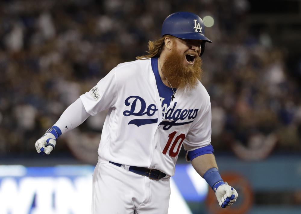 Justin Turner celebrates his game-winning three-run homer with two outs in the bottom of the ninth inning Sunday night, lifting the Dodgers to a 4-1 win over the Cubs in Game 2 of the National League Championship Series.