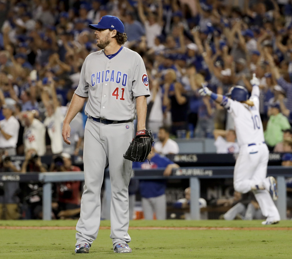 Justin Turner of the Dodgers celebrates after hitting a three-run game-ending home run off Cubs pitcher John Lackey, left, in the ninth inning of Game 2 of the NLCS on Sunday.