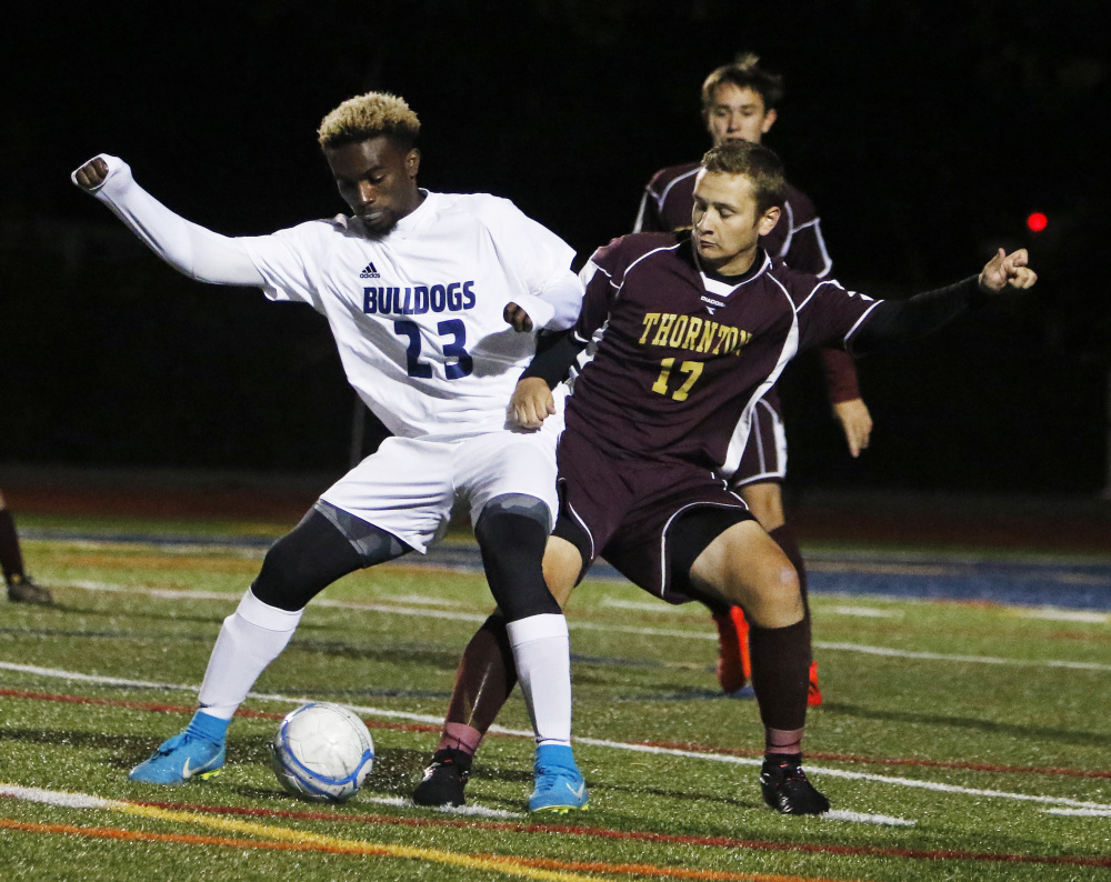 Pedro Fonseca of Portland tries to hold the ball against Thornton Academy's Jake Nason during their SMAA game Monday at Fitzpatrick Stadium. Portland won, 2-1, and will take a 10-3-1 record into the Class A South playoffs.