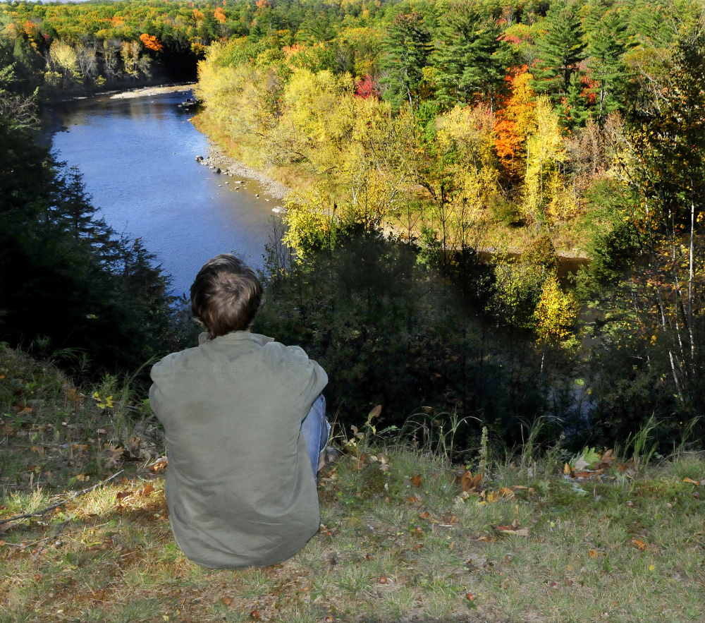 A Mercer resident, who declined to give his name, looks down on the Sandy River from his property Monday. He was rescued Sunday by firefighters from Skowhegan and Norridgewock after the ax he was wielding slipped, cutting him badly on an ankle.