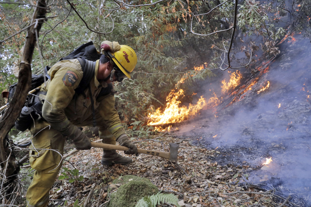A firefighter builds a containment line as he battles a wildfire Tuesday near Boulder Creek, Calif.