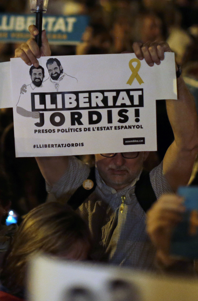 """A man holds a sign reading in Catalan """"Freedom"""" as people gather Tuesday in Barcelona, Spain, to protest against the National Court's decision Associated Press/Emilio Morenatti"""