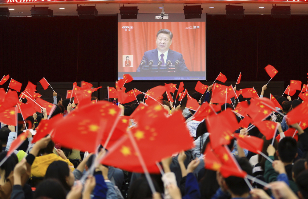 Students wave flags Wednesday as they watch a televised speech by President Xi Jinping during the opening ceremony of China's twice-a-decade party congress in Huaibei.