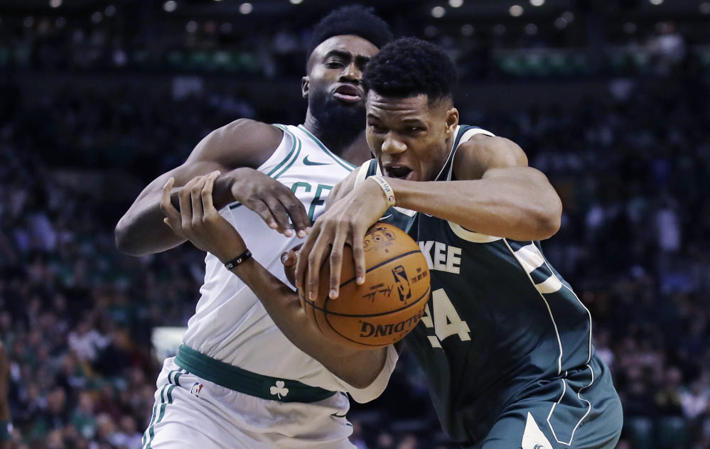 Milwaukee's Giannis Antetokounmpo, right, tries to drive past Boston's Jaylen Brown in the first quarter of Wednesday night's game at Boston.