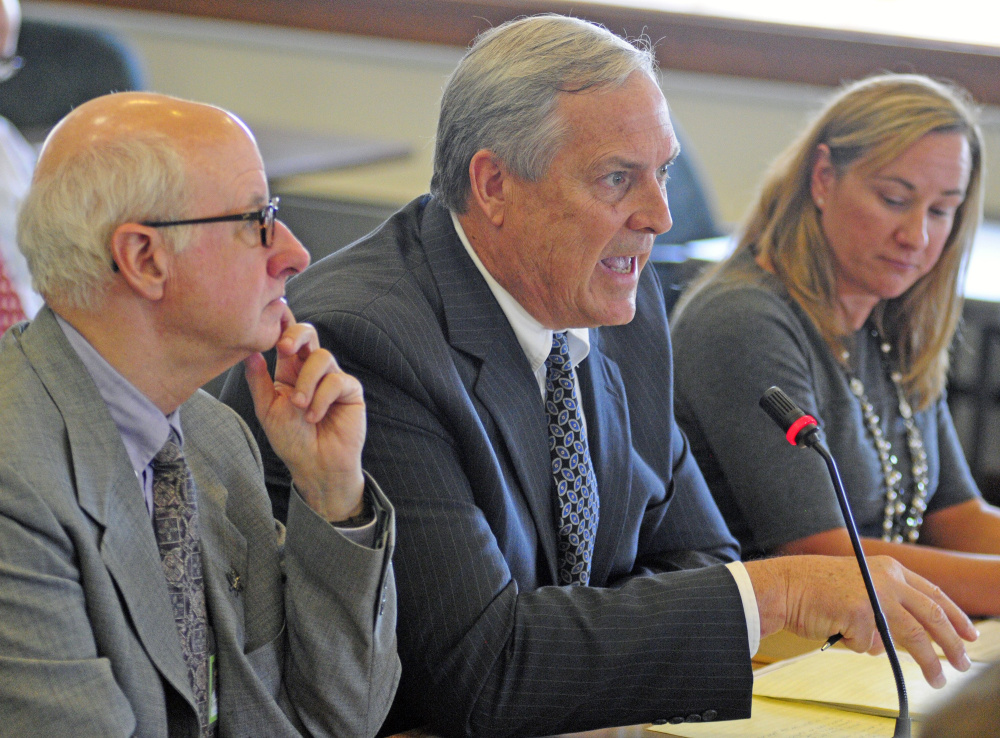 Ricker Hamilton, center, served as deputy commissioner of programs in the DHHS from 2013 until June. If confirmed as commissioner, he will head a department dogged by controversy and frequently in the public spotlight.