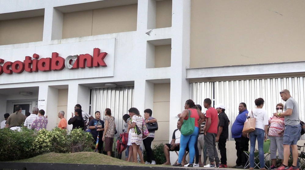 A long line of people waits to enter a branch of Scotia Bank on Saturday in Carolina, Puerto Rico. ATMs and credit cards don't work since there is no electricity and the only way to buy goods is by using cash.