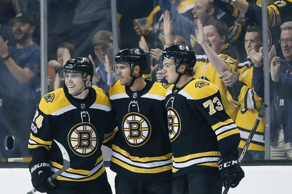 Boston's David Krejci, center, celebrates his goal with Jake DeBrusk, 74, and Charlie McAvoy in the first period Thursday night in Boston.