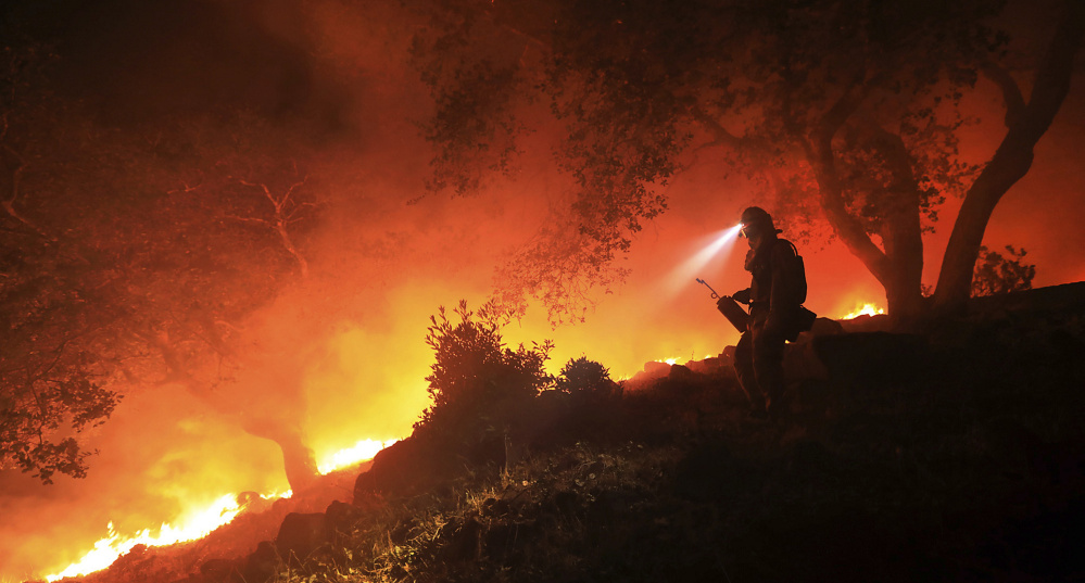 A San Diego firefighter monitors a flare-up on at the head of a wildfire off High Road above the Sonoma Valley on Oct. 11 in Sonoma, Calif. A wind shift caused flames to move quickly uphill and threaten homes in the area. Three days after the fires began, firefighters were still unable to gain control of the blazes that had turned entire Northern California neighborhoods to ash and destroyed thousands of homes and businesses.