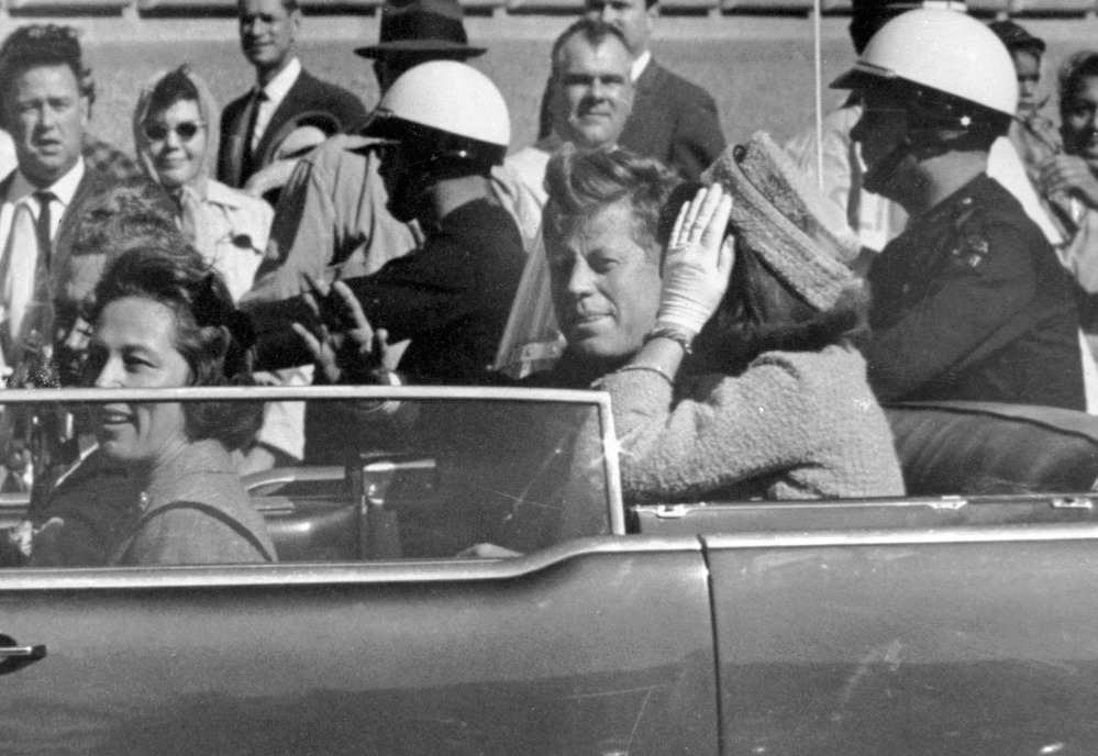 President John F. Kennedy waves from his car in a motorcade in Dallas. Riding with him are first lady Jacqueline Kennedy, right, Nellie Connally, second from left, and her husband, Texas Gov. John Connally, far left.