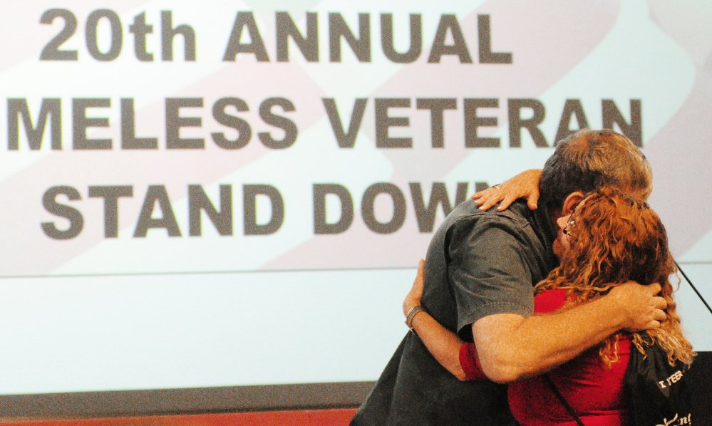 Robert Lindie of Augusta hugs social worker Susie Whittington after speaking Saturday at the 20th annual Homeless Veteran Stand Down at the VA at Togus.
