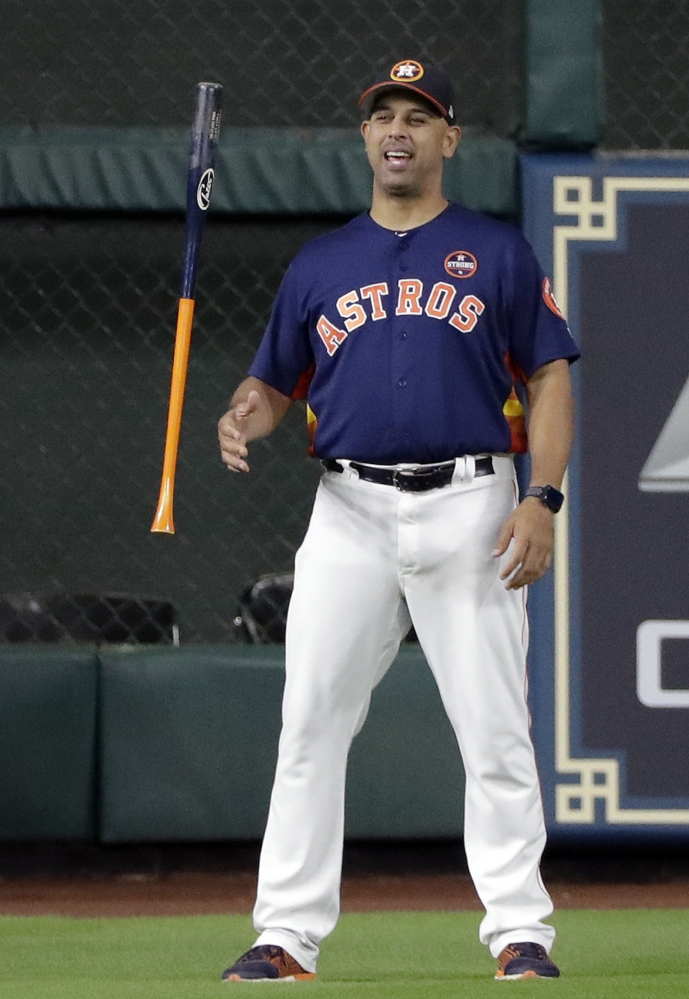 Houston bench coach Alex Cora flips a bat before Game 6 of the ALCS in Houston. The Boston Red Sox hired Cora to be their new manager.