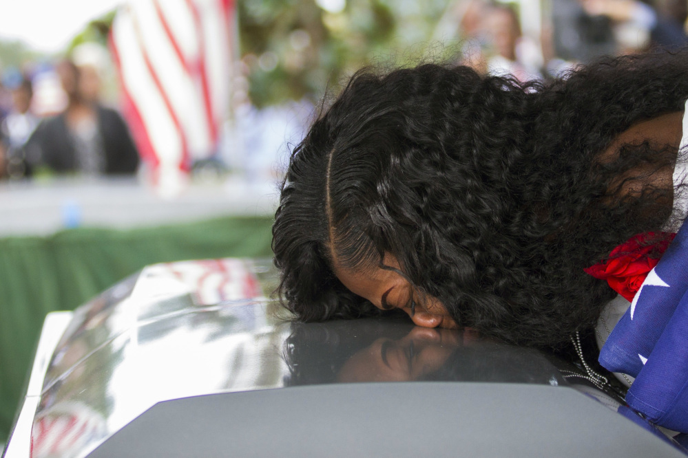 "Myeshia Johnson kisses the casket of her husband, Sgt. La David Johnson during his burial service at Fred Hunter's Hollywood Memorial Gardens in Hollywood, Fla. Myeshia Johnson told ABC's ""Good Morning America"" on Monday that she has nothing to say to the president, adding that his phone call to her made ""me cry even worse."""