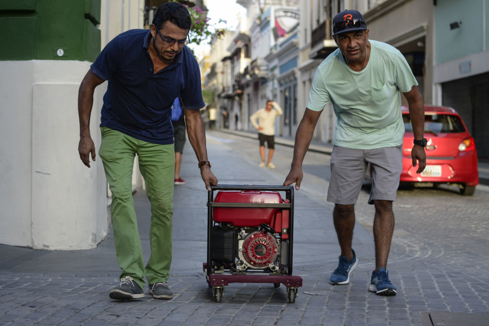 Residents push a generator along the street in San Juan, Puerto Rico, on Friday. In the month since Hurricane Maria, a third of the hotels remain shuttered and many shops and restaurants are closed.