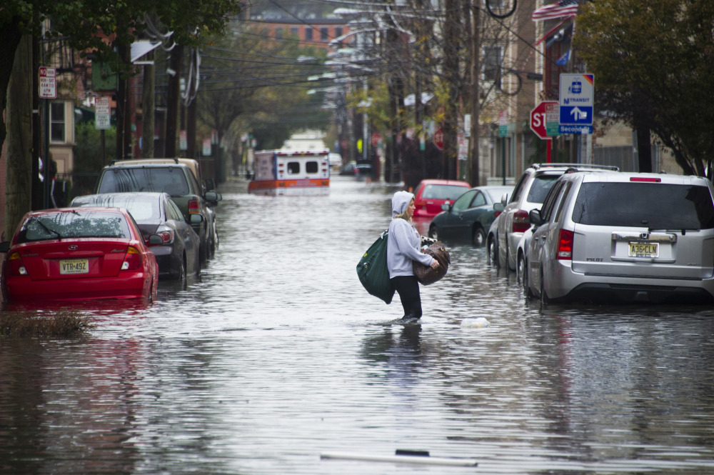 A woman walks through floodwaters in Hoboken, N.J., on Oct. 30, 2012, the day after Superstorm Sandy struck the coasts of New York and New Jersey.