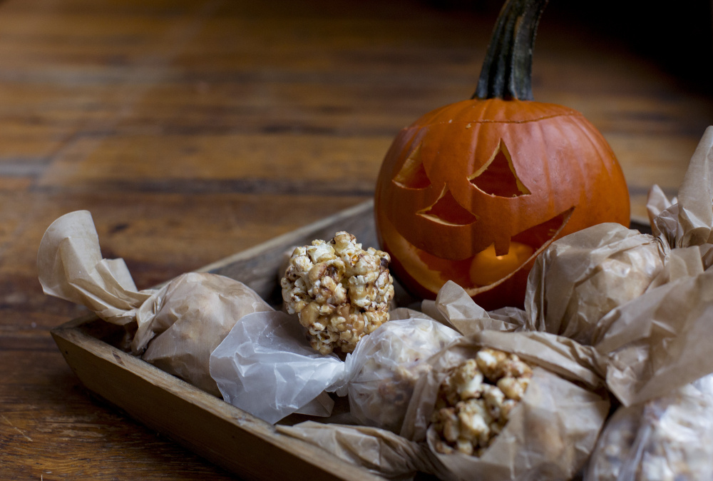 Honey, peanut butter and chocolate popcorn balls are a great Halloween treat to munch on while you are handing out candy to kids.
