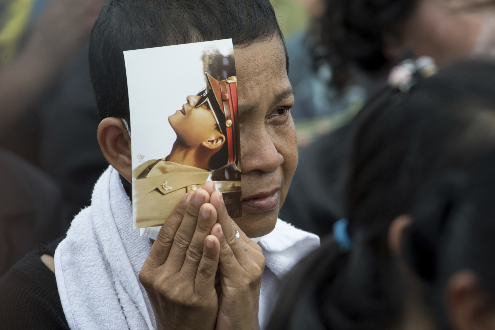 A Thai mourner holds a portrait of King Bhumibol Adulyadej.
