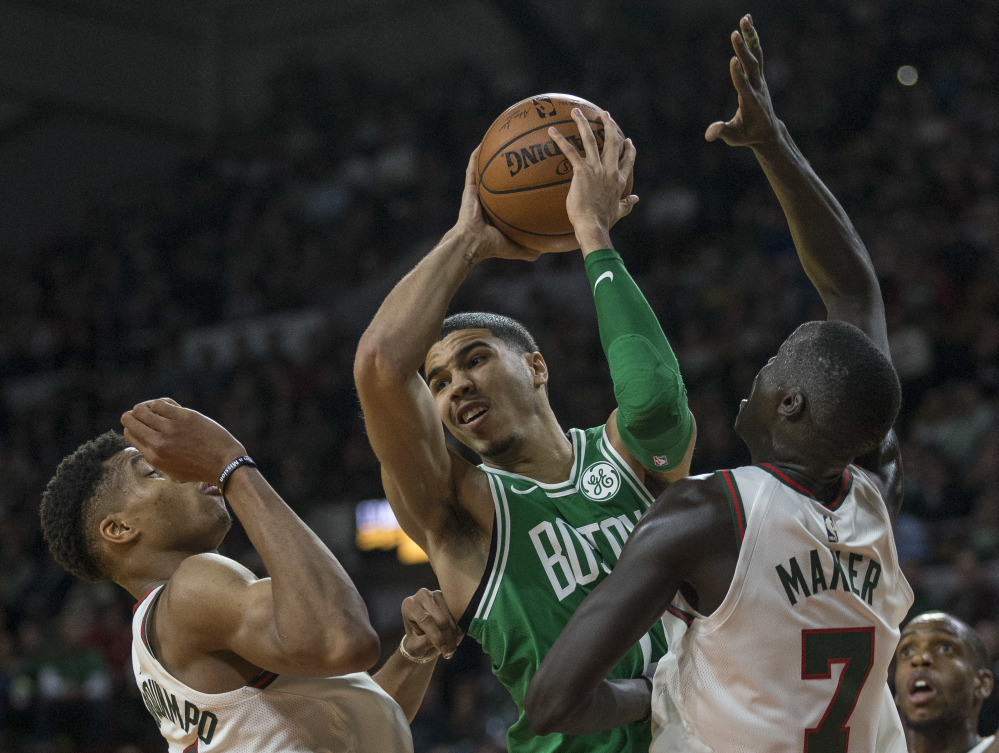 Boston's Jayson Tatum looks to pass the ball after being stopped by Milwaukee's Giannis Antetokounmpo and Thon Maker in the second half Thursday night in Milwaukee.