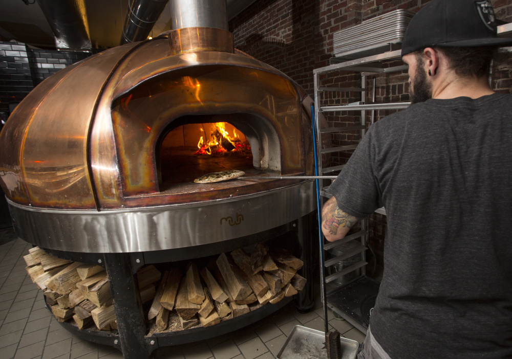 Bradley Foster works the wood-fired Le Panyol oven, the copper surface of which remains cool to the touch even when the temperature of the deck inside hits 750 degrees.