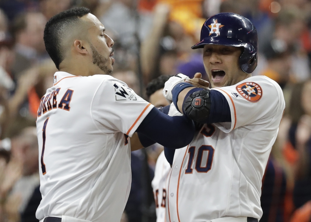 Houston's Yuli Gurriel is congratulated by Carlos Correa after hitting a home run in the second inning Friday night in Houston in Game 3 of the World Series.