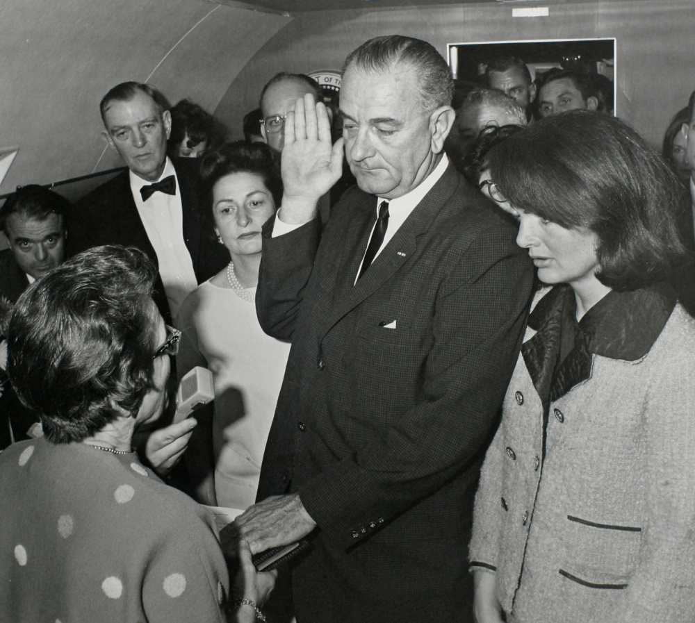 Vice President Lyndon Johnson takes the oath of office as President Kennedy's widow, first lady Jacqueline Kennedy, stands at his side.