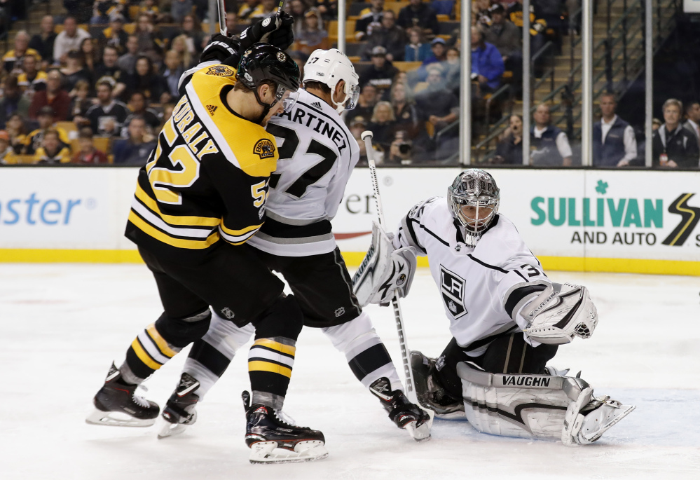 Los Angeles Kings goalie Jonathan Quick makes a glove save as Bruins' Sean Kuraly looks for a rebound during the second period in Boston on Saturday.