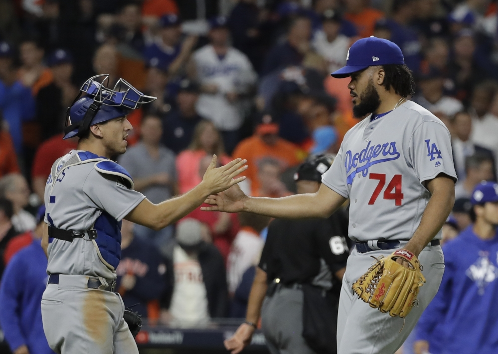 Los Angeles closer Kenley Jansen shakes hands with catcher Austin Barnes at the end of Game 4 of the World Series on Saturday night in Houston. The Dodgers won 6-2 to tie the series at 2.