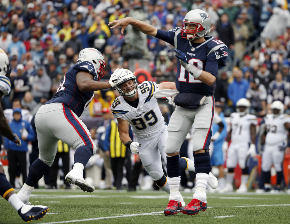 New England Patriots quarterback Tom Brady passes under pressure from Los Angeles Chargers defensive end Joey Bosa during the first half Sunday in Foxborough, Mass.