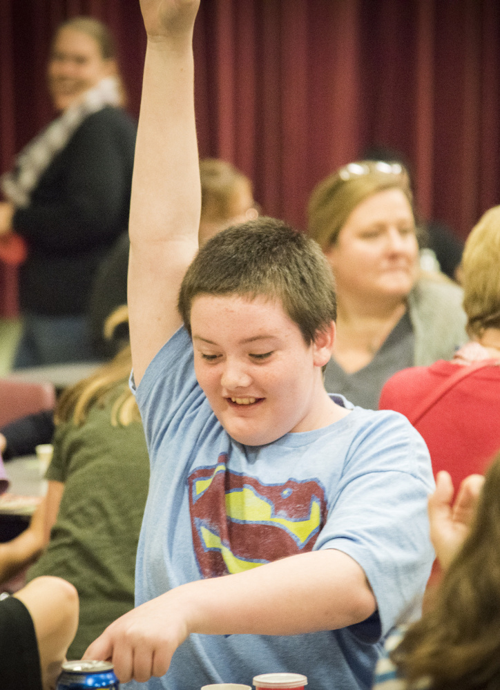 "Hunter Ward, 11, of Winslow raises his hand indicating ""bingo"" at Winslow Elementary School."