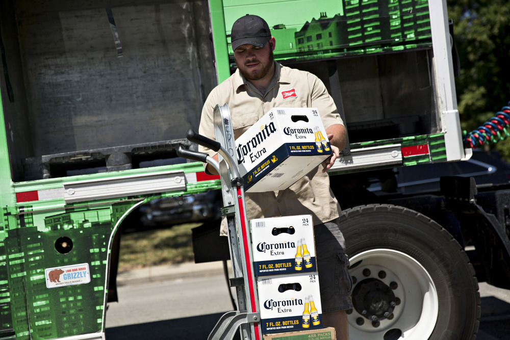 A worker loads cases of Constellation Brands' Corona beer onto a cart for delivery in Ottawa, Illinois, on June 27, 2017. (MUST CREDIT: Daniel Acker/Bloomberg)