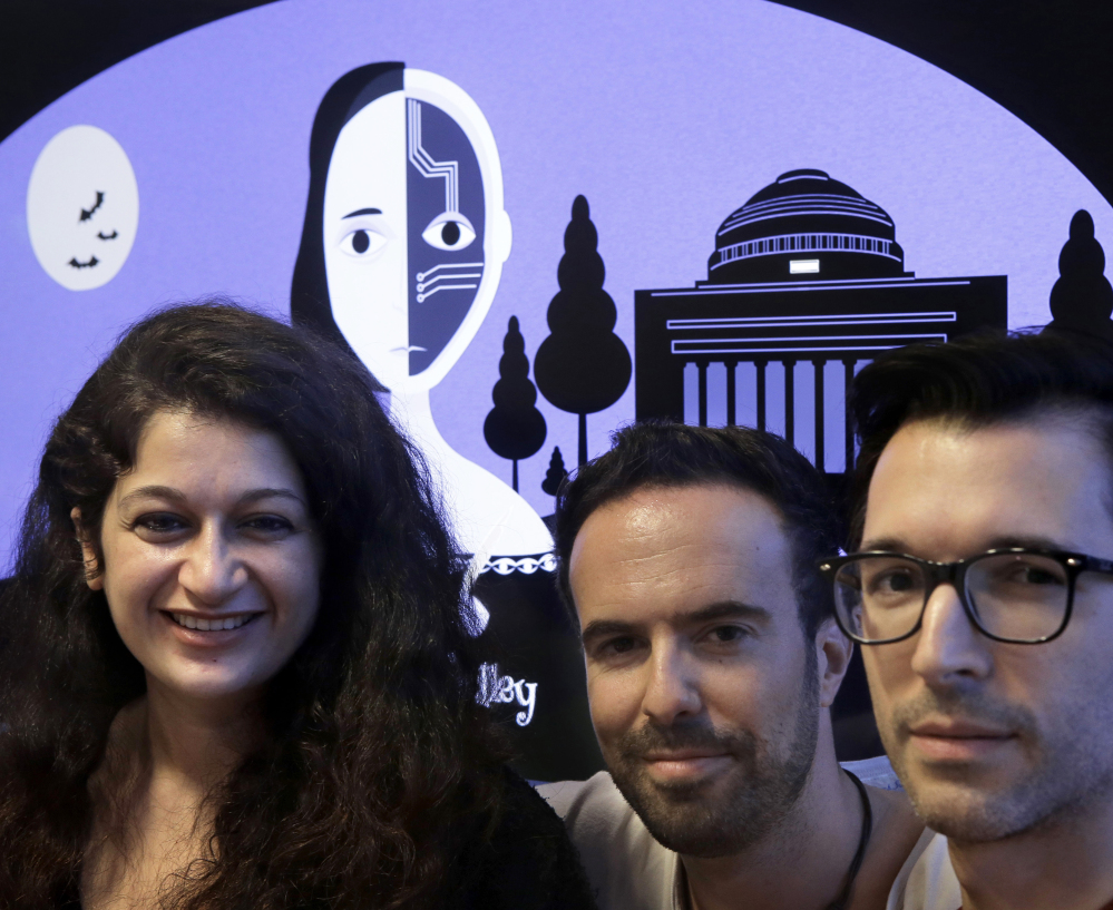 "From left, MIT researchers Pinar Yanar- dag, Manuel Cebrian and Iyad Rahwan developed a ""bot"" that generates horror stories on Twitter. Behind them is a graphic from the website home page."