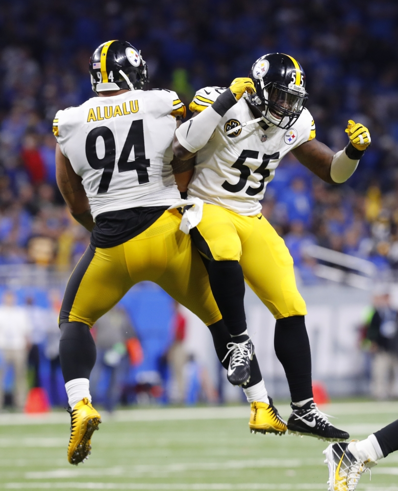 Steelers defenders Tyson Alualu, left, and Arthur Moats celebrate after teammate JuJu Smith-Schuster's record 97-yard TD reception Sunday.