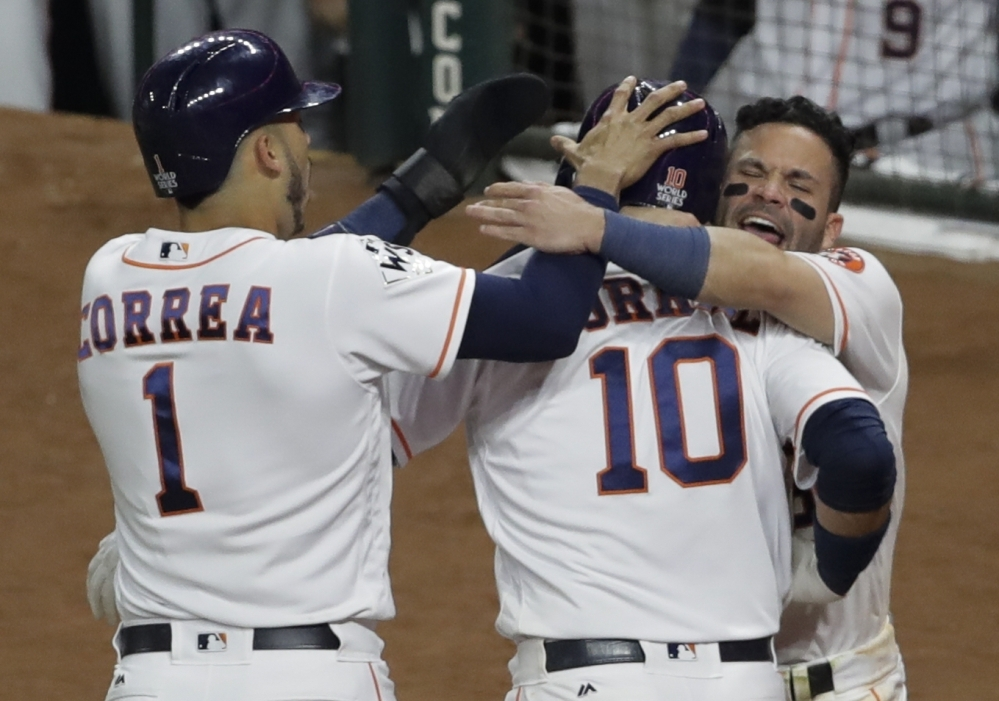 Houston's Yuli Gurriel is congratulated after hitting a three-run home run in the fourth inning of Game 5, which the Astros finally won 13-12 in the 10th inning early Monday morning.