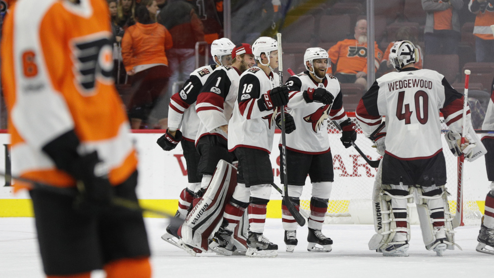 Arizona's Alex Goligoski, center right, celebrates with goalie Scott Wedgewood, right, after Goligoski's goal late in overtime gave the Coyotes their first win of the season, 4-3 over the Flyers in Philadelphia on Monday night.